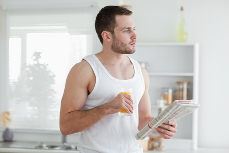 Young man drinking orange juice while reading the news in his kitchen photo