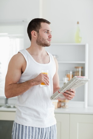 Portrait of a young man drinking orange juice while reading the news in his kitchen photo