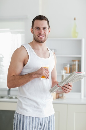 Portrait of a smiling man drinking orange juice while reading the news in his kitchen photo