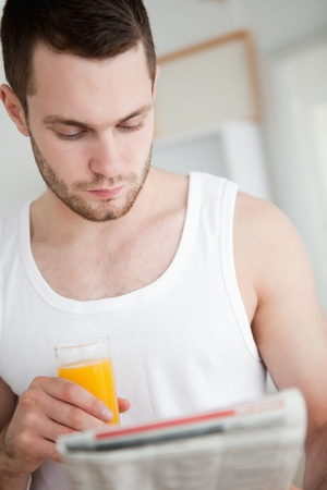 Portrait of a beautiful man drinking orange juice while reading the news in his kitchen photo