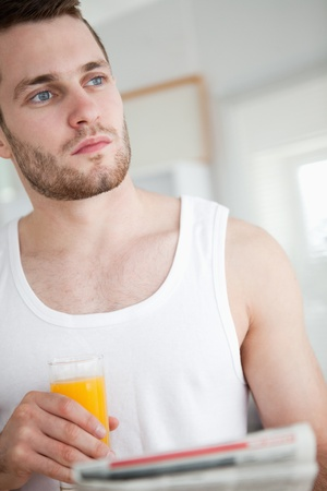 Portrait of a good looking man drinking orange juice while reading the news in his kitchen photo