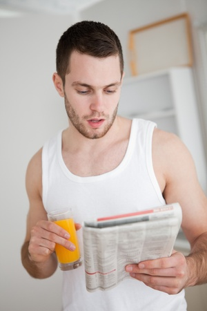 Portrait of a young man reading the news while drinking orange juice in his kitchen photo