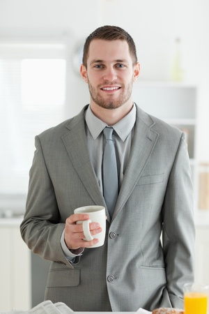 Portrait of a businessman having breakfast in his kitchen photo