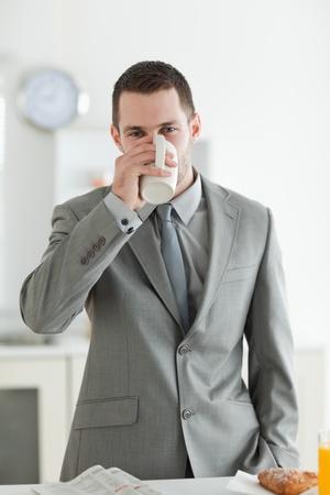Portrait of a handsome businessman having breakfast in his kitchen photo