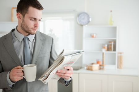 Businessman drinking coffee while reading the news in his kitchen photo