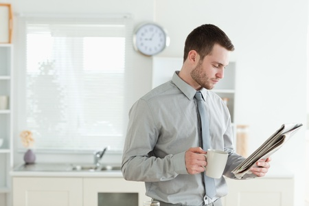 Young businessman reading the news while having breakfast in his kitchen photo