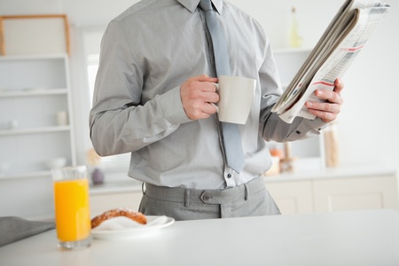 Businessman holding a newspaper while having breakfast in his kitchen photo