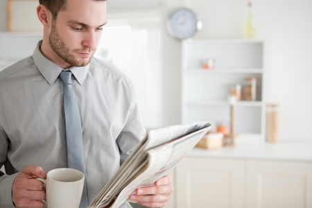 Businessman reading a newspaper while drinking tea in his kitchen photo