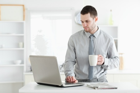 read news: Businessman using a laptop while drinking coffee in his kitchen Stock Photo