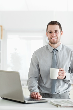 Portrait of a businessman using a notebook while drinking coffee in his kitchen photo