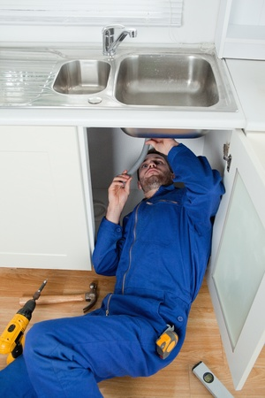 home maintenance: Portrait of a smiling plumber fixing a sink in a kitchen Stock Photo