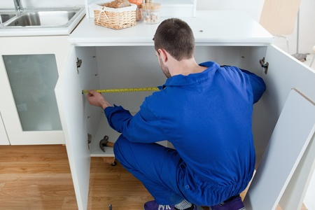 Repair man measuring something in a kitchen Stock Photo - 11632292