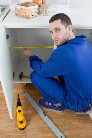 Portrait of a young repair man measuring something in a kitchen Stock Photo