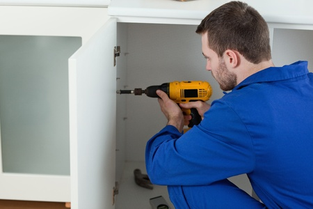 work workman: Young handyman fixing a door in a kitchen Stock Photo