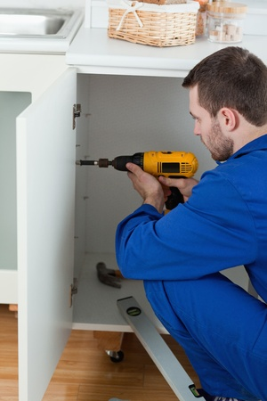 Portrait of a handyman fixing a door in a kitchen photo