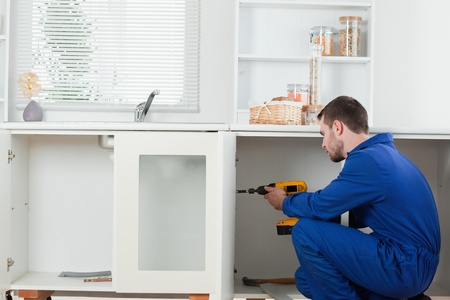 Good looking handyman fixing a door in a kitchen Stock Photo - 11632546