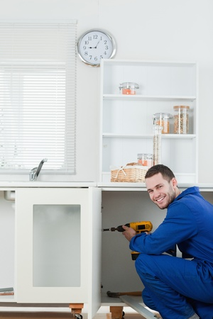 Portrait of a smiling handyman fixing a door in a kitchen photo