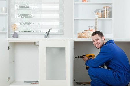 Smiling handyman fixing a door in a kitchen photo