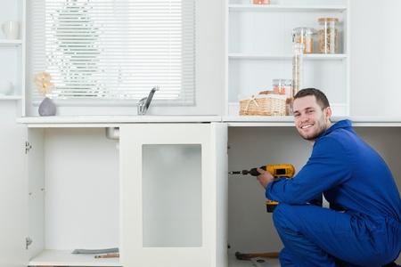 Happy handyman fixing a door in a kitchen photo