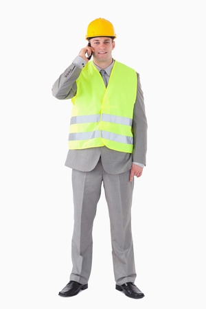 Portrait of a young builder making a phone call against a white background photo
