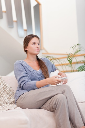 Portrait of a young woman watching TV in her living room Stock Photo - 11632390