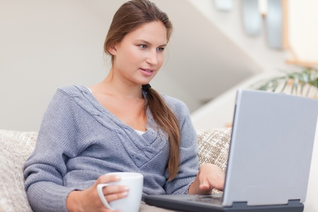 Woman using a laptop while having a coffee in her living room photo
