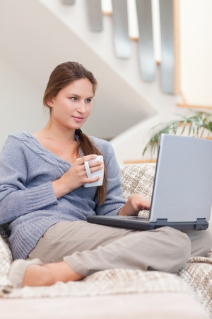 Portrait of a woman using a laptop while having a tea in her living room photo