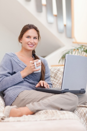 Portrait of a woman using a laptop while having a coffee in her living room photo