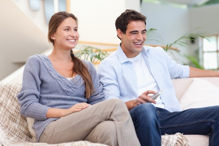 Couple watching TV in their living room photo