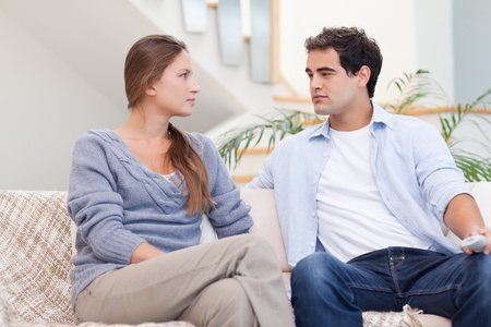 Couple having an argument while watching TV in their living room photo