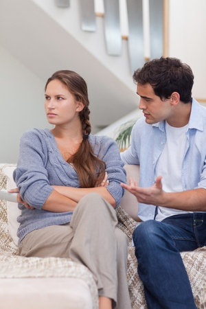 to argue: Portrait of a woman being mad at her boyfriend in their living room Stock Photo
