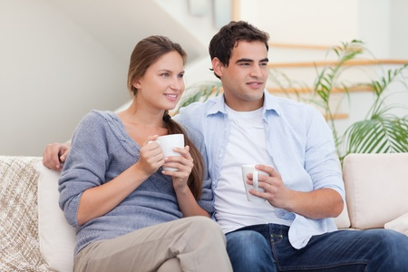 Couple watching TV while drinking tea in their living room photo