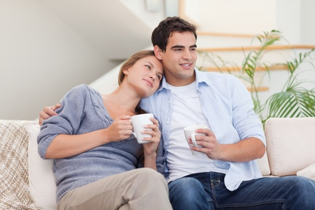 Lovely couple watching TV while drinking tea in their living room photo