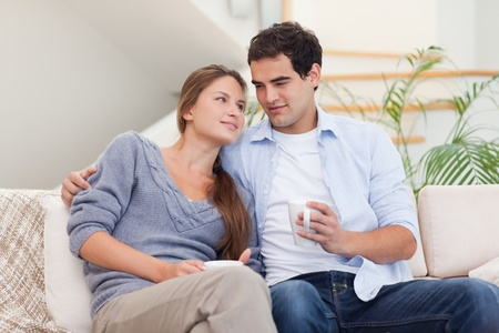Couple watching TV while drinking coffee in their living room photo
