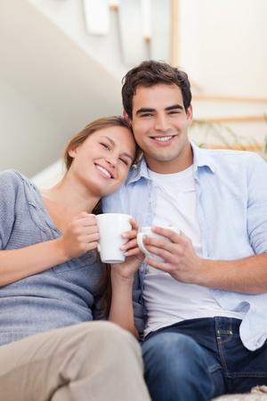 drinking coffee: Retrato de una pareja tomando caf� en su sala de estar