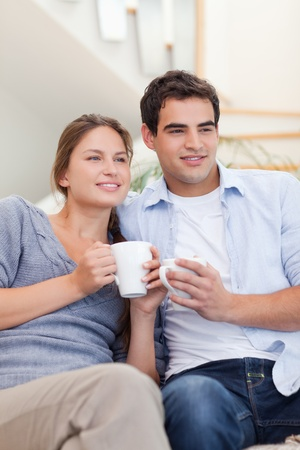 Portrait of a couple drinking coffee while watching TV in their living room photo