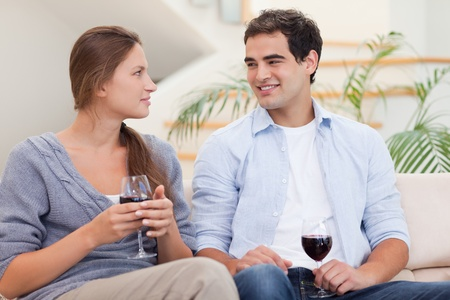 Couple having a glass of red wine while looking at each other Stock Photo - 11632701