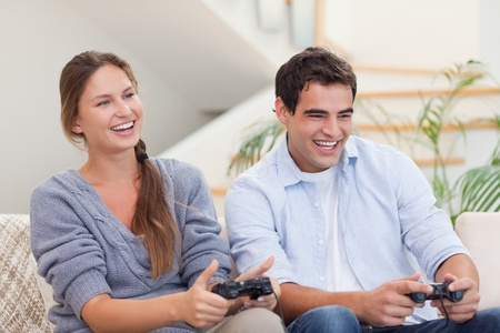 Smiling couple playing video games in their living room photo