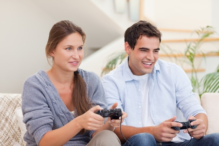 Young couple playing video games in their living room photo