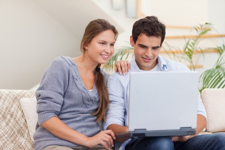 Smiling couple using a laptop in their living room photo