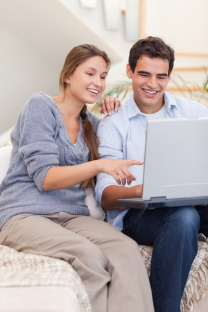 Portrait of a couple using a laptop in their living room photo