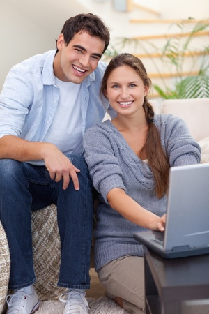 Portrait of a radiant couple using a notebook in their living room photo