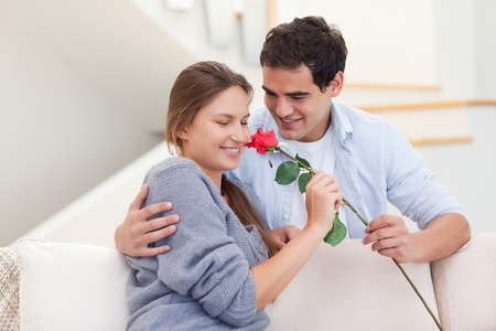 Young man offering a rose to his fiance in their living room photo