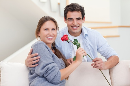 Young man offering a rose to his wife in their living room photo