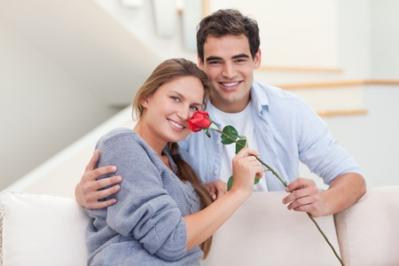 Young man offering a rose to his girlfriend in their living room photo