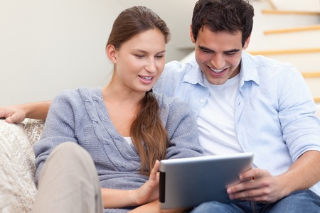 Couple using a tablet computer in their living room photo
