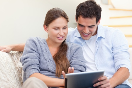 Happy couple using a tablet computer in their living room photo