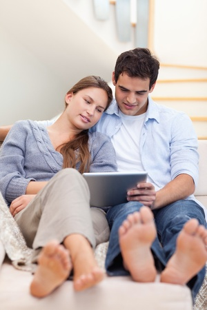 Portrait of a couple using a tablet computer in their living room Stock Photo - 11632732