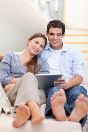 Portrait of a young couple using a tablet computer in their living room Stock Photo - 11632684