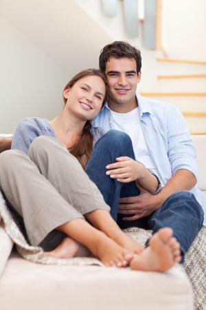 Portrait of a couple lying on a sofa while looking at the camera Stock Photo - 11632584